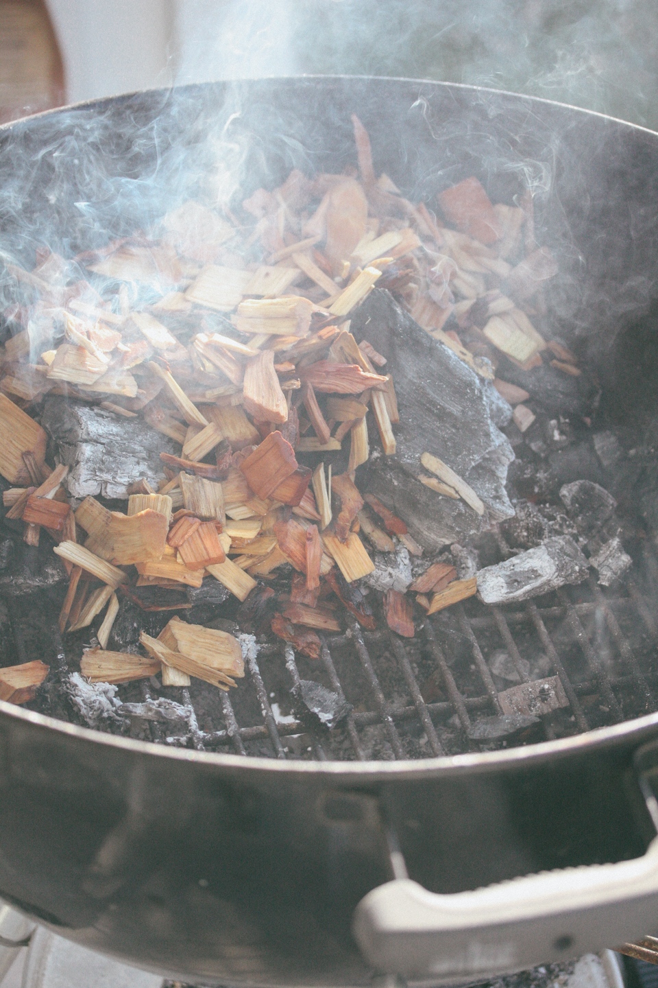 Pour the coals to one side of the Weber and place the wood chips on top of the coal